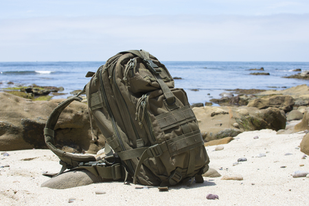 Green military backpack sitting on sandy beach with rocky ocean coastline in background on sunny day Stock Photo