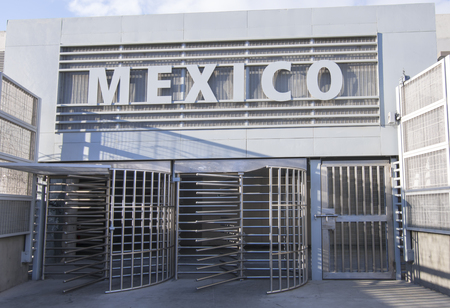 Mexico sign and turnstile revolving gates at pedestrian border crossing from San Ysidro, United States to Tijuana, Mexico early in morning with no people