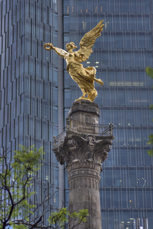 Telephoto shot of beautiful gold statue of Angel of Independence perched on top of monument column with high rise in background on cloudy day in Mexico City Stockfoto