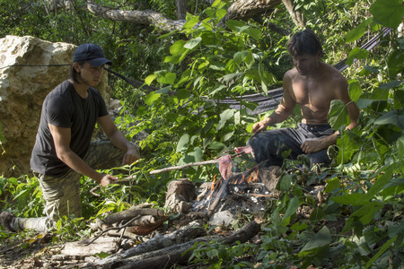 Two adventure explorers cooking meat over primitive campfire in tropical rainforest surrounded by dense vegetation in Chiapas, Mexico Stockfoto