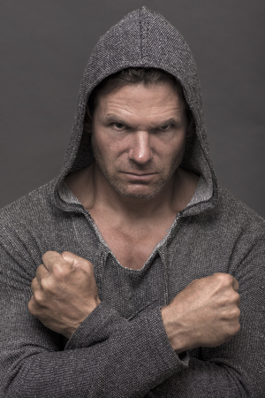 Intense expression of tough Caucasian man wearing gray hoodie sweater and flexed fists crossed on gray background