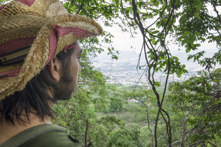 Closeup wide angle from behind over shoulder of Hispanic adventure man looking at city of Tuxtla Gutierrez from top of hill in jungle through window of tropical vegetation in Chiapas, Mexico Stock Photo