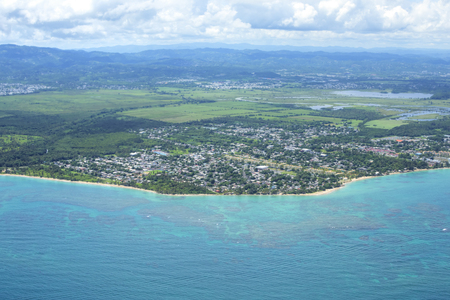 Aerial view of Caribbean coastline and urban town with mountains in background at Vieques, Loiza, Puerto Rico on sunny day