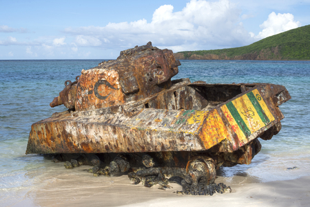 Rusty old Sherman tank partially submerged in water and sand on Flamenco Beach of Caribbean island of Isla Culebra in afternoon sunlight Stockfoto