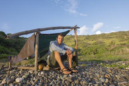 Male castaway sitting at simple camp next to coconut on pebble beach of Caribbean island of Isla Culebra in morning light