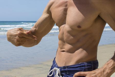 Closeup shirtless tan Caucasian man flexing abs on sandy beach under sunny sky