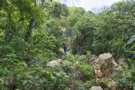 Wide angle adventurous male hiker standing on boulder drinking water from canteen in middle of dense tropical jungle in Chiapas, Mexico