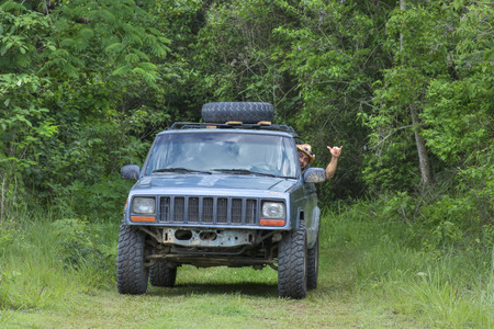 Handsome Hispanic male adventurer smiles while making hang loose hand sign while driving off road in truck through tropical forest in Chiapas, Mexico Stock Photo