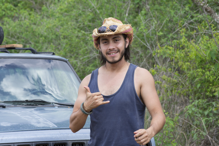 Handsome male Hispanic adventurer smiles and makes hang loose sign with hand in front of truck parked in wilderness Stockfoto