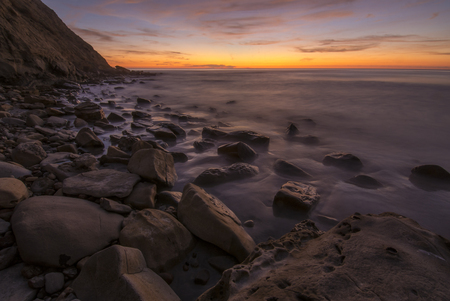 Boulder covered beach at bottom of cliff of Scripps Coastal Reserve in La Jolla, California after sunset