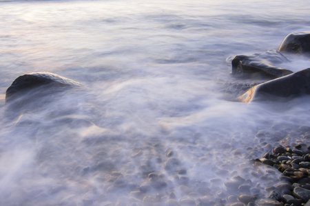 Slow shutter dreamy effect of surf flowing over pebblestone and rocky shore of ocean