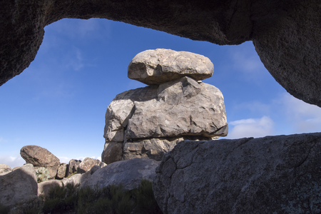 View of massive boulders stacked upon each other as seen from nearby cave at top of Teutonia Peak in Mojave National Preserve in California on sunny day Stockfoto