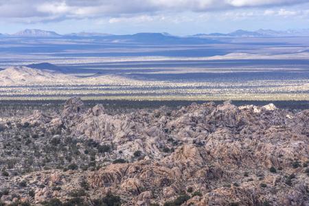 Clouds cast horizontal shadows across arid rugged desert landscape of Mojave National Preserve in California on northwest side of Teutonia Peak Stock fotó