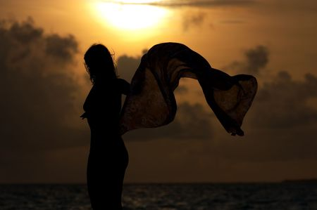 Young girl dancing on the beach at sunset photo