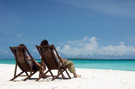 흰 모래 해변에 앉아있는 젊은 부부