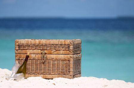 luna de miel: la cesta, el vino y dos cristales del vino en la arena blanca varan