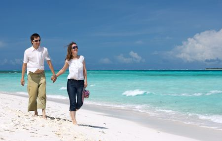 Young happy couple walking along tropical beach photo