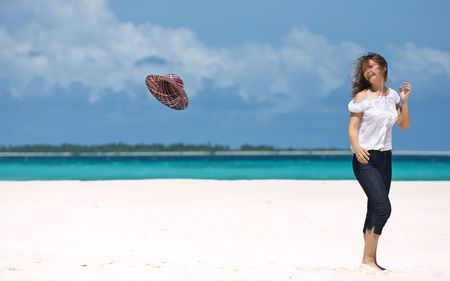 Happy girl on white sand beach looking to flying hat and smiling photo