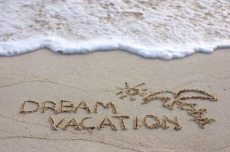 """""""Dream vacation"""" note written on white sand and ocean wave"""