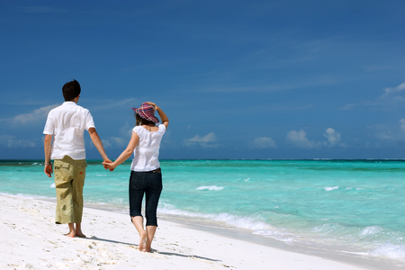 Young loving couple walking along tropical white sand beach