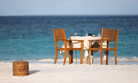 Dining table prepared for two on white sand beach close to the ocean