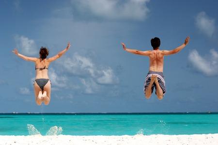 happy couple having fun on the beach jumping Stock Photo