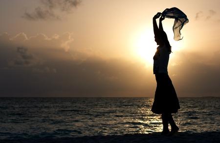 scarf beach: silueta de la muchacha joven que baila en la playa en la puesta del sol