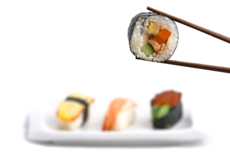 nigiri: Japanese food: delicious Futomaki (big roll) hold with chopsticks and selection of three nigiri shushes isolated on white background Stock Photo