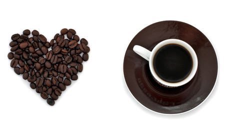 Coffee beans making heart shape and cup of fresh aromatic coffee isolated on white background photo