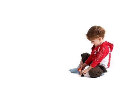 Cute de 3 a�os de edad vestido casual ni�o jugando con los juguetes. Aislado en fondo blanco.  Foto de archivo - 1576951