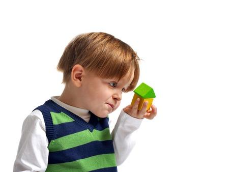 droomhuis: Is dat mijn droom huis Cute 3-jarige jongen op zoek naar kleine huis gebouwd van houten blokken. Geïsoleerd op witte achtergrond. Stockfoto