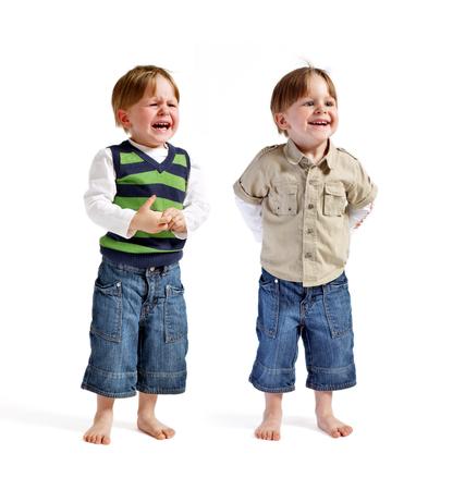 ni�os tristes: Doble serie: Uno se enfrentan a dos emociones. Dos ni�os gemelos muy lindo (una sonriente, otra llorando) aisladas en el fondo blanco. Foto de archivo