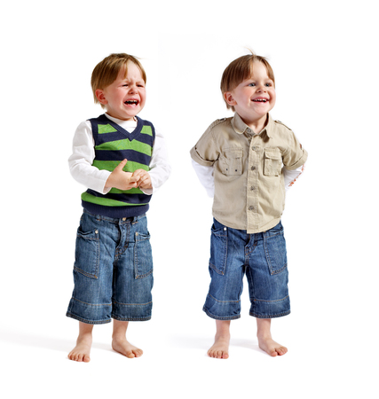 beautiful sad: Twin series: One face two emotions. Two very cute twin boys (one smiling, another one crying) isolated on white background.