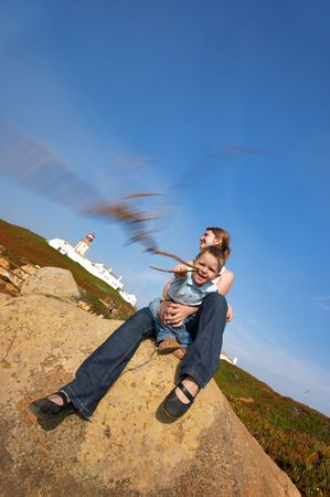 roca: Family fun at Europe?s edge. Mother and son having fun together. Lighthouse of Cabo da Roca ? west most point of Europe ? is on background