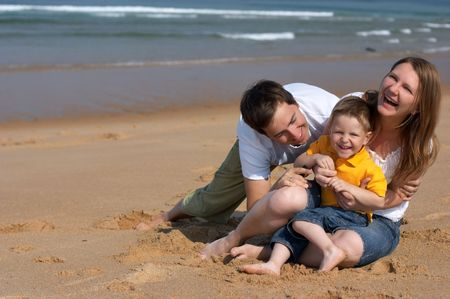 Happy family of three having fun at the beach Stock Photo - 1888344