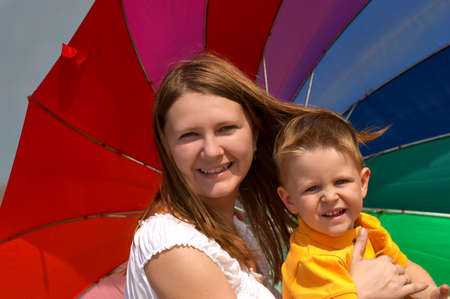 bight: Happy young woman and kid under brightly colored umbrella having fun outdoors.