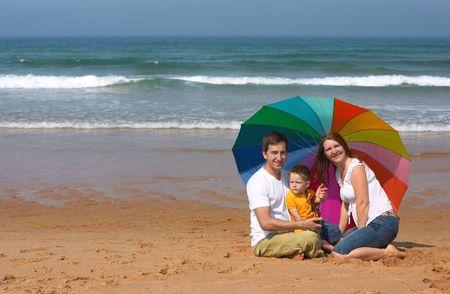 Happy family of three having fun at the beach photo