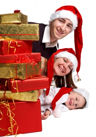three wishes: Isolated studio shot of happy young family of three wearing Santa�s hats with a lot of Christmas presents. Stock Photo