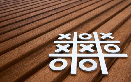 Tic Tac Toe game on wooden surface photo