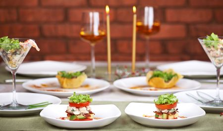 Romantic candlelight dinner with three dishes set for two. Focus on the two closest appetizers with tomatoes and lettuce.  photo