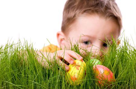 pascuas navide�as: Caza de huevos de Pascua. Cute muchacho en busca de huevos de pascua ocultos en la hierba verde fresca. Aislado en fondo blanco  Foto de archivo
