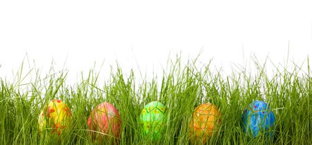 Row of five Easter eggs in fresh green grass