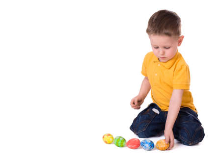 Cute 3-years old boy playing with Easter eggs. Isolated on white. photo