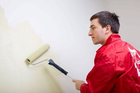 overall: Hombre pintando una pared. Pintor en general de pintura roja en la pared de color verde claro  Foto de archivo