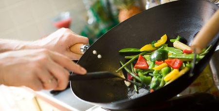 chef cocinando: Chef de cocina verduras en wok pan
