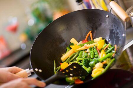 Chef cooking vegetables in wok pan