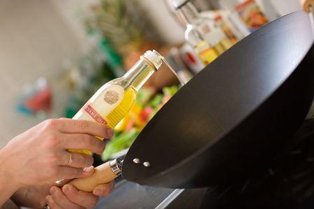 sezam: Chef wlewając olej sezamowy na patelni wok
