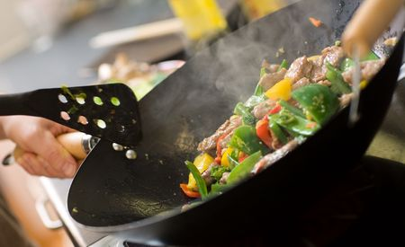 pan: Chef cooking vegetables and meat in wok pan