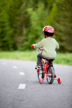 3 years old boy wearing safety bicycle helmet riding a bike photo