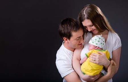 Studio picture of happy young parents and newborn girl over dark gray background Stock Photo